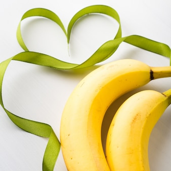 Two bananas with green ribbon frame and heart symbol