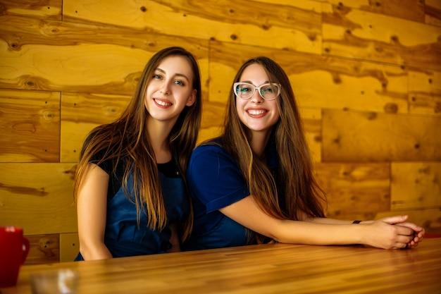 Двое друзей-бариста в кафе улыбаются