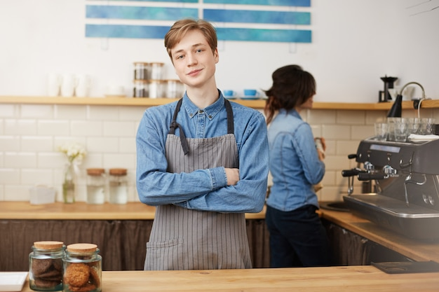 Two baristas working at bar counter in coffee shop.