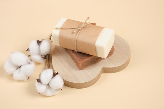 Два кусочка домашнего мыла ручной работы на деревянной подставке в форме сердца и цветка хлопка, бежевый фон экологичный уход за телом