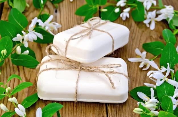 木の板の背景に、より糸、葉のある小枝、スイカズラの白い花で結ばれた白い石鹸の2本の棒