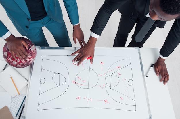 2人のバスケットボールのコーチが新しいゲーム戦略を計画して話し合います