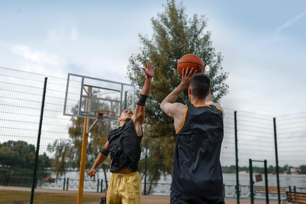 Два баскетболиста играют на открытой площадке.