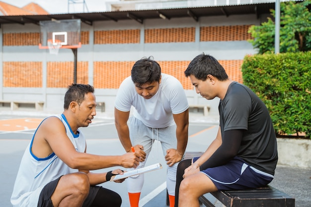 Two basketball players heeding a coachs instructions using a clipboard
