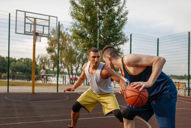 야외 코트에서 강렬한 경기를 두 농구 선수.