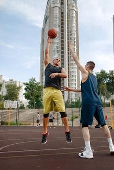 야외 코트에서 노는 두 농구 선수.