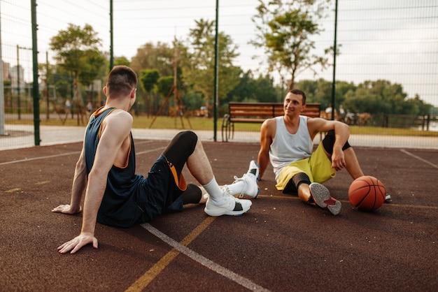 야외 코트에서 바닥에 앉아 두 농구 선수