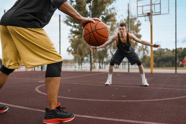 Two basketball players work out tactics on outdoor court.