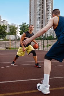 Two basketball players work out tactics on outdoor court