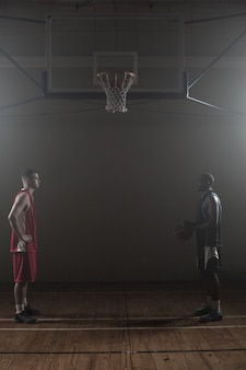 Two basketball rival looking each other face to face
