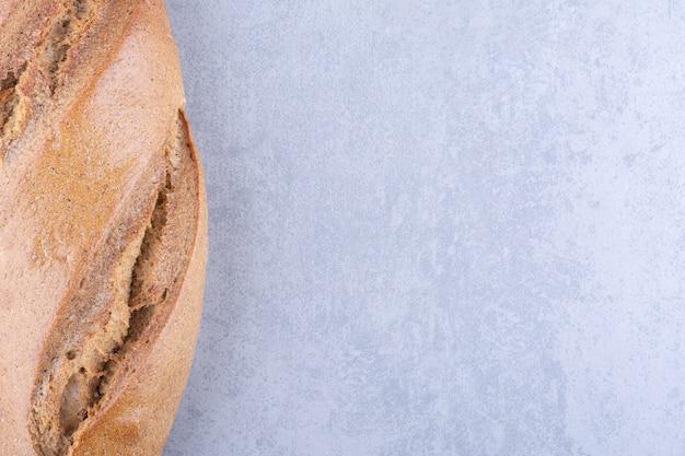 Due pagnotte di pane a bastone impilate su una superficie di marmo