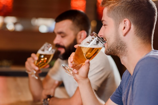 Two bearded men drinking beer in cafe.