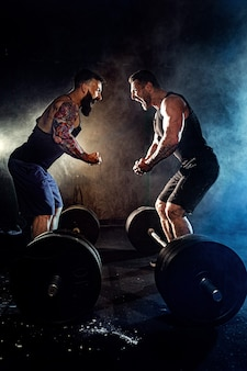 Two bearded tattooed muscular men look at each other and shout in the gym.