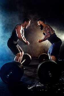 Two bearded tattooed muscular men look at each other and shout in the gym