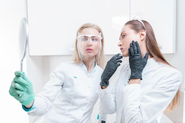 두 미용사가 손에 거울을 들고 의료 살롱에서 포즈를 취합니다. 회춘 개념. 혼합 매체