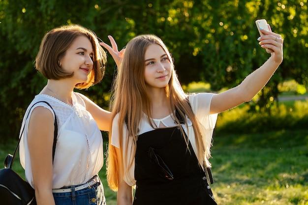 Две красивые подруги-школьницы (студентки) делают селфи по телефону в парке
