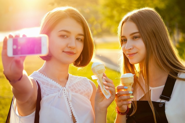 2人の美女の最高のガールフレンドの女子学生(学生)が公園で電話で自分撮りをします