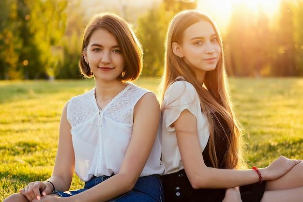 公園の芝生の上に座っている2人のbeautifu最高のガールフレンド女子学生(学生)