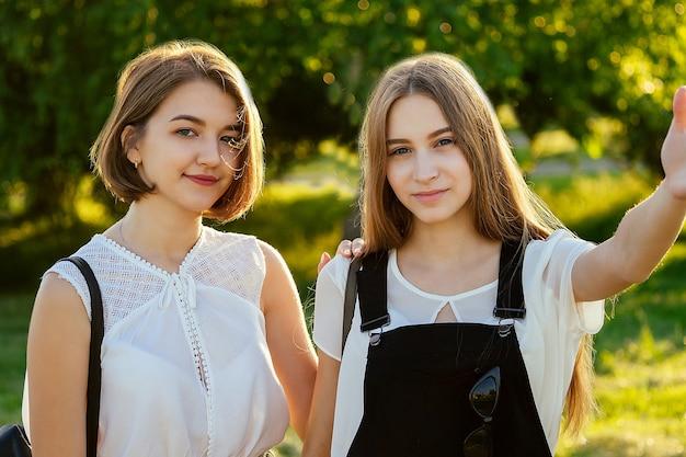 Две красивые девушки-подростки делают селфи по телефону в парке