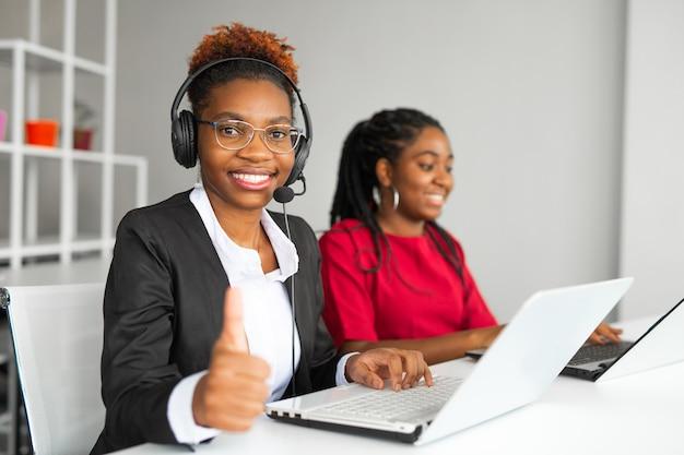 Две красивые африканские молодые женщины в офисе за столом с ноутбуком