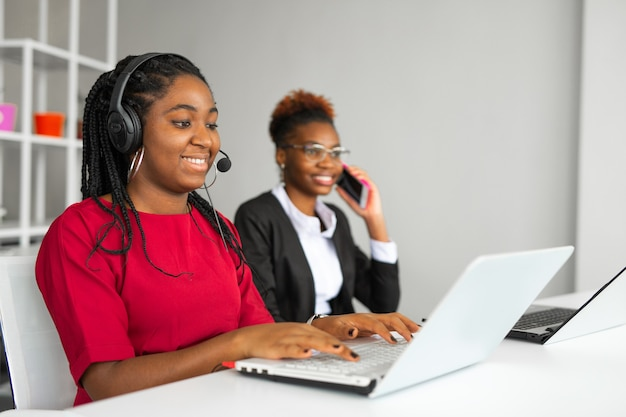Two beautiful african young women in the office at the table with a laptop
