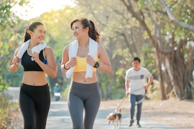 2人の美しく魅力的なフィットネスの女の子が晴れた朝に公園でジョギングしています