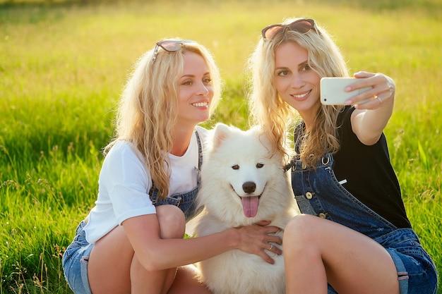 公園で電話で座って自分撮りをしている白いふわふわのサモエド犬と2人の美しく魅力的な金髪の双子の女性。