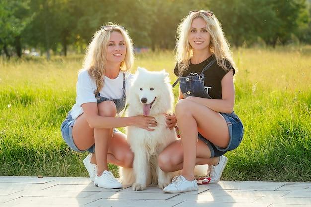 公園に座っている白いふわふわサモエド犬と2人の美しく魅力的な金髪の双子の女性。
