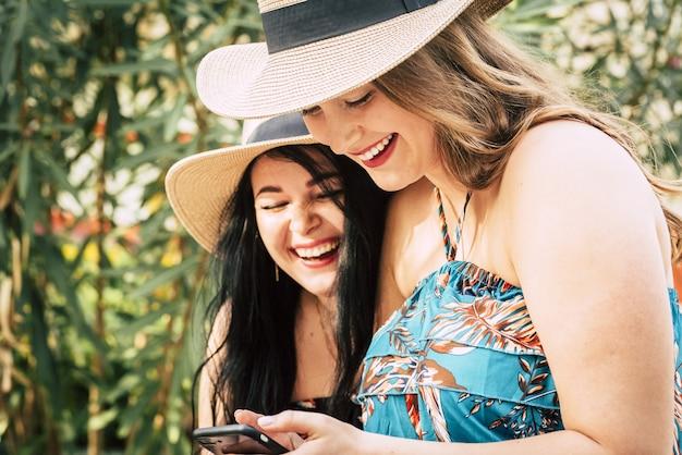 夏休みに屋外で携帯電話を使って楽しいテキストメッセージを楽しんでいる麦わら帽子をかぶった2人の美しく陽気な女性観光客。携帯電話を使用して2人の楽しい女性の友人