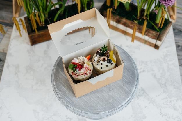 ギフトボックスの明るい背景に2つの美しく、おいしいトライフルケーキのクローズアップ。デザート、健康食品。