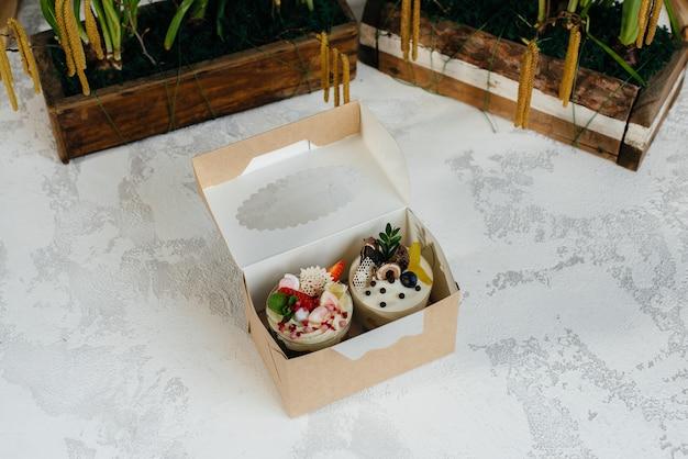ギフトボックスの明るいスペースに2つの美しくておいしいトライフルケーキのクローズアップ。デザート、健康食品。