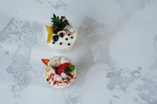 明るい表面に2つの美しくておいしいトライフルケーキのクローズアップ。デザート、健康食品。