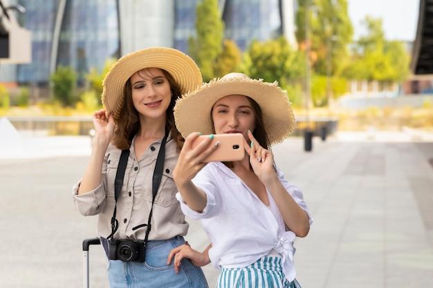 기차역에서 selfie를 복용 두 아름답고 행복한 여성 관광 여자.