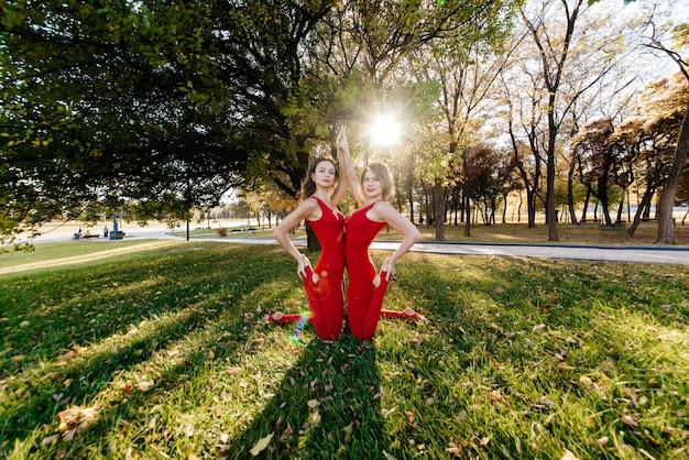 Две красивые и счастливые молодые женщины делают упражнения йоги и в парке в солнечный день в макро