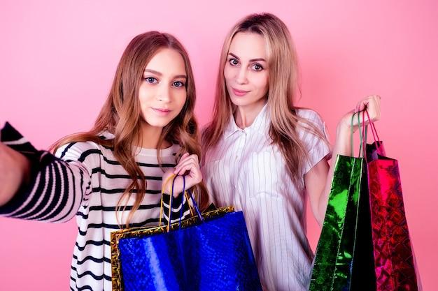 たくさんの買い物袋を持って、スタジオのピンクの背景に電話で自分撮りをする2人の美しくて笑顔の女性(母と娘)。販売とショッピングの概念