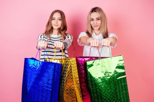 スタジオでピンクの背景にたくさんの買い物袋を持っている2人の美しくて笑顔の女性(母と娘)。販売とショッピングの概念