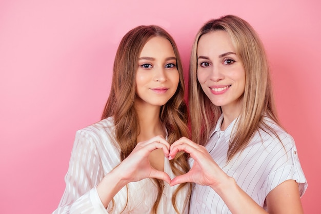 두 명의 아름답고 웃는 여성 엄마와 딸이 스튜디오의 분홍색 배경에서 하트 제스처를 합니다. 사랑과 가족의 개념입니다.