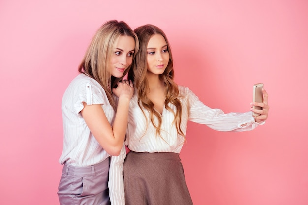 Две красивые и улыбающиеся подружки (мать и дочь) делают селфи на телефоне на розовом фоне в студии. концепция эгоизма и себялюбия