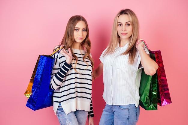 スタジオでピンクの背景にたくさんの買い物袋を持っている2人の美しくて笑顔の女性のガールフレンド。販売とショッピングの概念