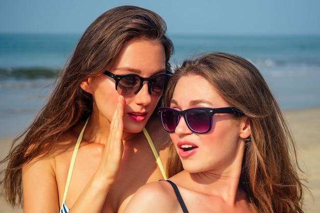 두 아름답고 젊은 여성이 해변에서 가십.