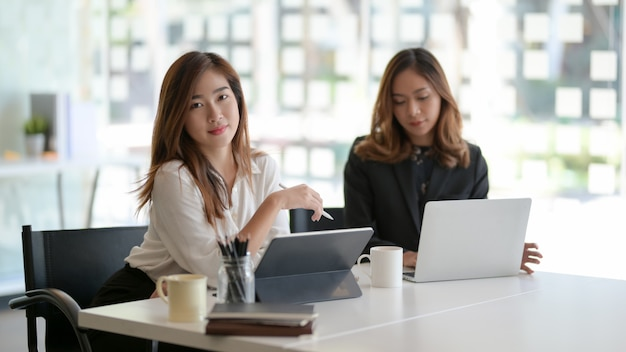 Two beautiful asian businesswomen working on their project together