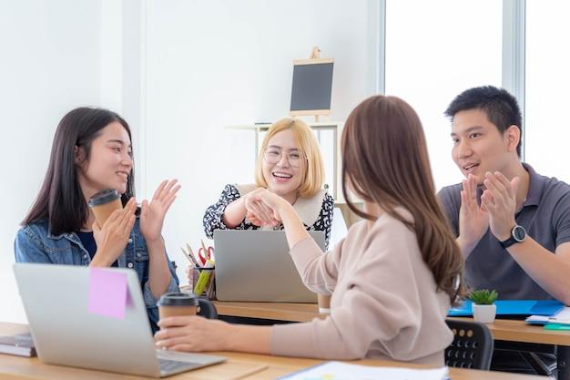 彼らの同僚がオフィスのテーブルで手をたたく間、握手し、笑顔でお互いを見ている2人の美しいアジアの女の子