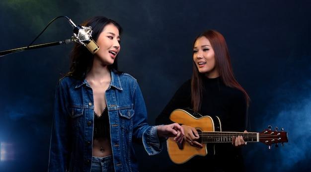 Две красивые азиатские певицы поют песни и играют на гитаре на сцене кафе