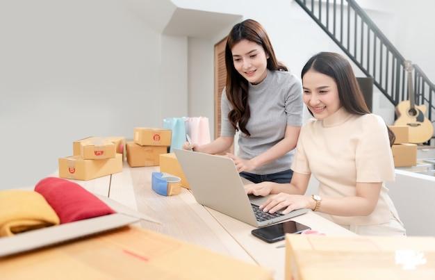 Две красивые азиатские женщины проверяют заказы через ноутбуки через интернет.