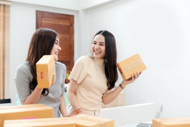 두 명의 아름다운 아시아 여성이 골판지 상자를 집어 들고 있습니다. 행복한 웃는 얼굴로 새로운 정상적인 온라인 비즈니스