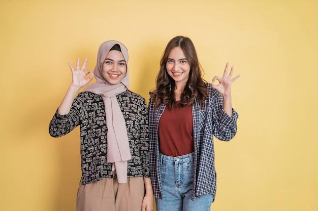 カメラを見ているときにok承認の手のジェスチャーで笑っている2人の美しいアジアの女性