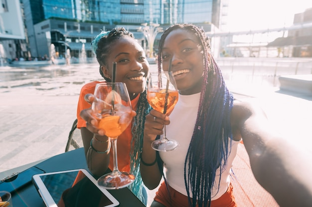 Two beautiful black women sisters sitting bar making a toast smiling