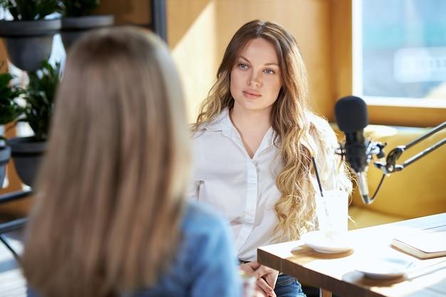 Две красивые женщины-блоггеры общаются в кафе