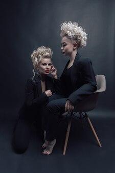 黒のスタジオで一緒にポーズをとる2つの美しいブロンドの髪のモデル