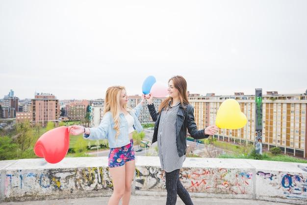 2つの美しいブロンドとブルネットの女の子が風船で遊ぶ